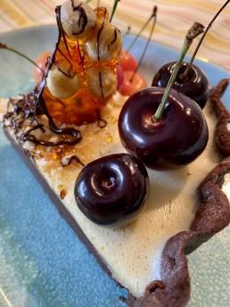 A slice of dark and white chocolate tart with hazelnut praline and fresh cherries