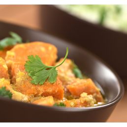 a bowl of colourful sweet potato curry with coriander garnish