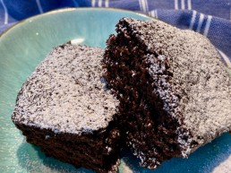 Two squares of sticky gingerbread cake dusted with icing sugar