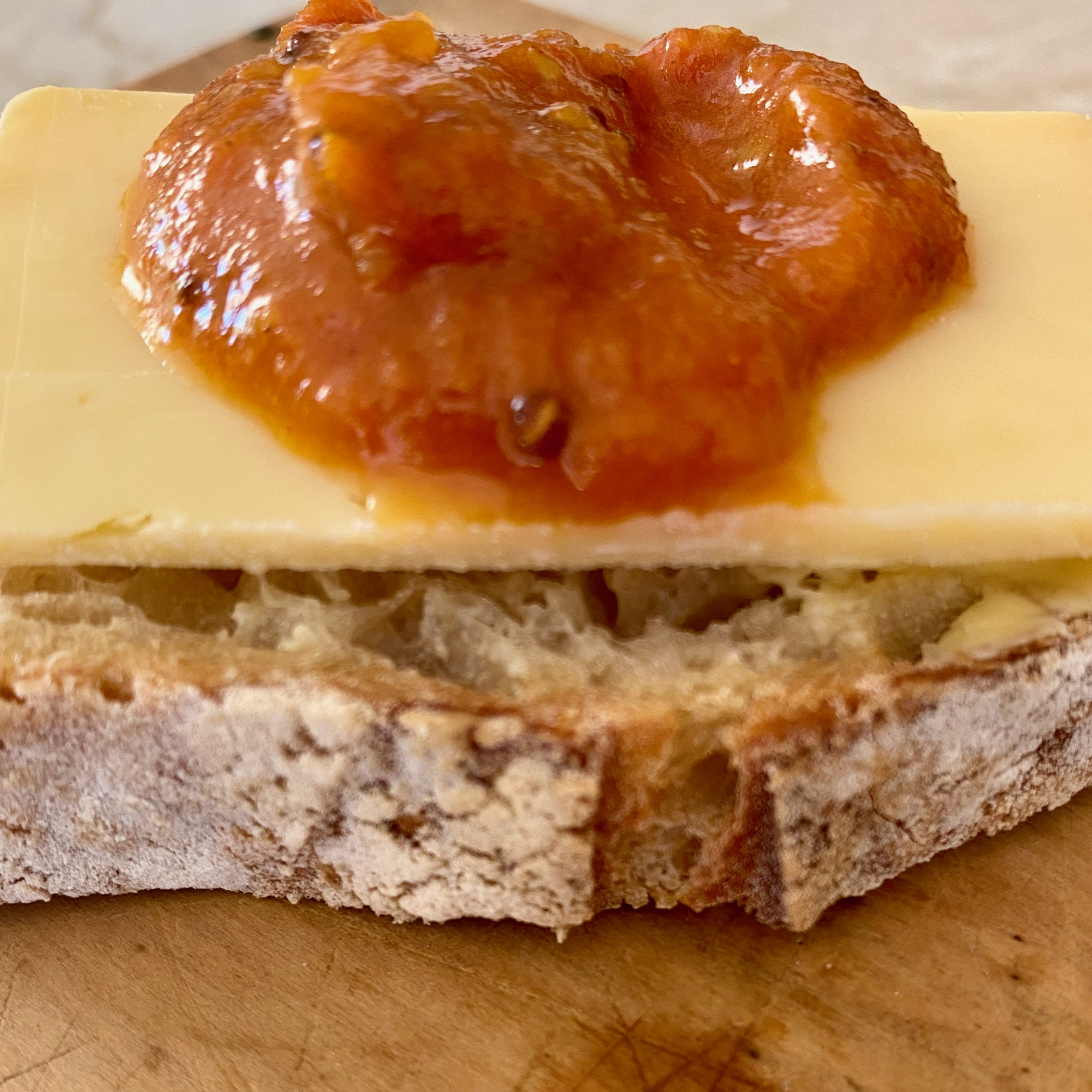 A slice of smoked cheddar cheese with pickle